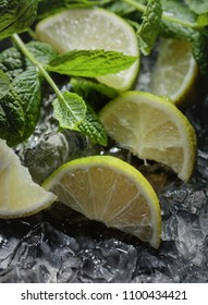 Lime slices with ice and mint on dark background. Selective focus .