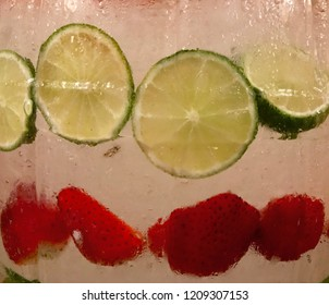 Lime slices and strawberries in a water cooler