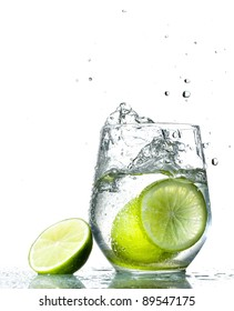 Lime splashing into glass of water on white background