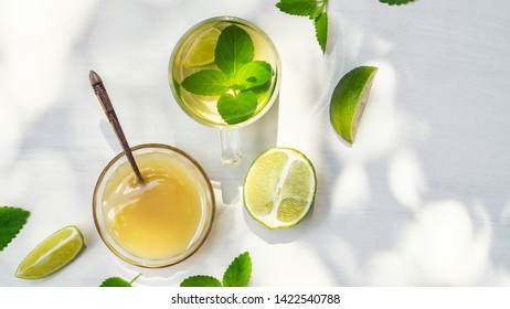 Lime tea with mint in a glass cup and honey on a white background with sunbeams
