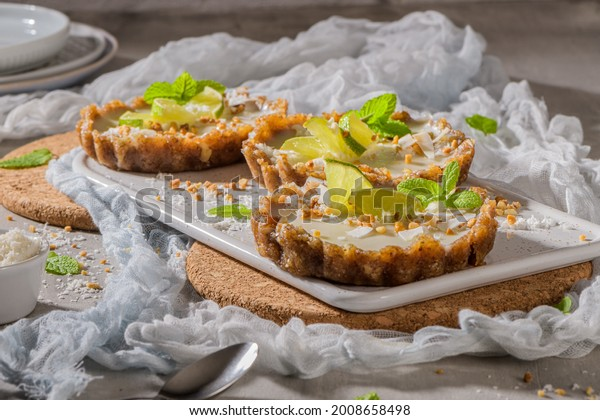 Lime vegan tarts with grated coconut  and crunchy peanuts. Citrus cake. Date, walnut, almond and hazelnut base.