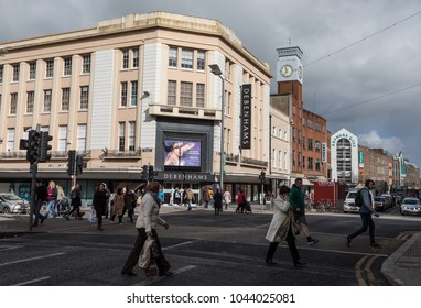 Limerick  City, Ireland -  7th March, 2018: People crossing the street in front of debenhams department store in Limerick city, Ireland.