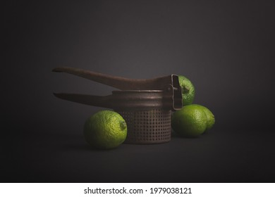 Limes and juicer on dark background