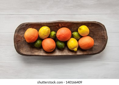 Limes, Lemons and Orange Citrus Fruit in a Vintage Wood Tray on a Whitewashed White Wood Background