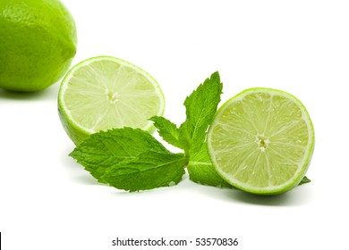 Limes with mint leaves over white background