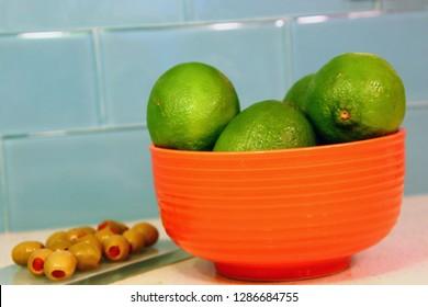 Limes in orange bowl and green olives on granite counter bar with blue glass tile back splash.