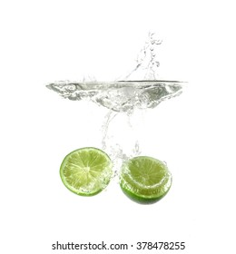 Limes splash on water, isolated on white background. Use for fresh drinks advertising. Advertising cocktails. Juicy fruits. Being shot as they submerged under water. Healthy form of product promotion.