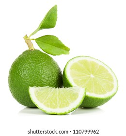 Limes whole and slices with green leaves. Isolated on white