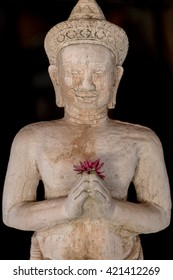 Limestone Buddhist statue with colored flower in hand isolated on back background. Thailand. Selective focus