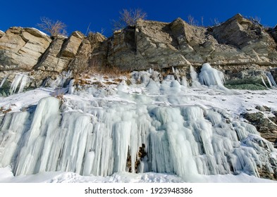 Limestone cliffs in Paldiski on the shores of the Baltic Sea with icicles in winter. clear sunshine and blue sky. Paldiski, Estonia