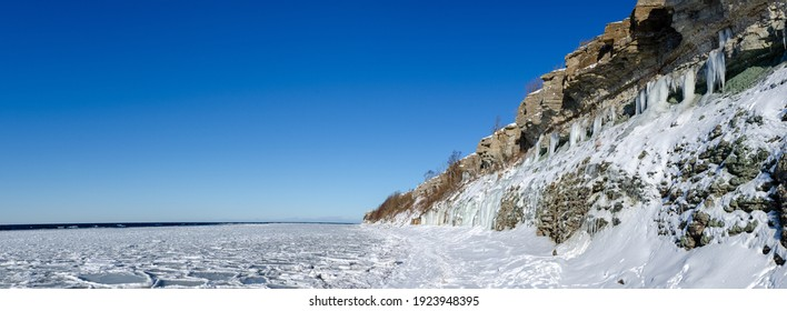 Limestone cliffs in Paldiski on the shores of the Baltic Sea with icicles in winter. clear sunshine and blue sky. Paldiski, Estonia. panorama