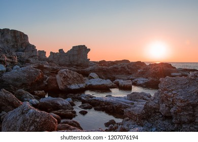 Limestone formations by the shore during peachy sunset in Gotland, Sweden