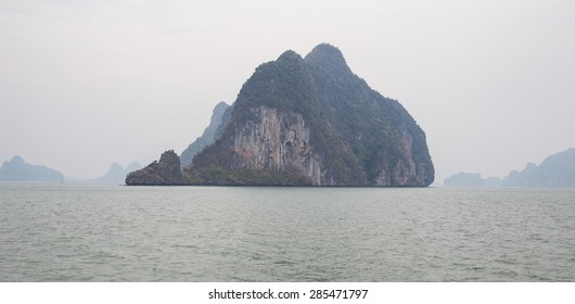 Limestone islands with Karst topography surrounded by water in the south of Thailand near Phuket. Rocky islands in the mist on the Adaman Sea in the Indian Ocean.