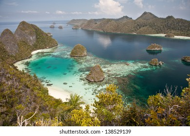Limestone islands in Raja Ampat, Indonesia, are surrounded by warm, clear waters that support healthy coral reefs.  This region is known for its high marine biological diversity and great diving.