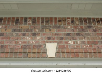 Limestone keystone construction detail above doorway in brick home with deep overhang soffit with vents. Weep holes in brick. Soldier courses in brick.