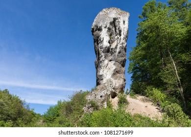 "Limestone monadnock, rock called ""Maczuga Herkuklesa"" (Hercules cudgel or bludgeon). Jurassic rock formation with Pieskowa Skala Castle in the background in Ojcow National Park near Krakow"