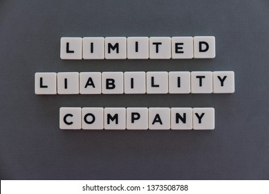 Limited liability company (LLC) word made of square letter word on grey background.
