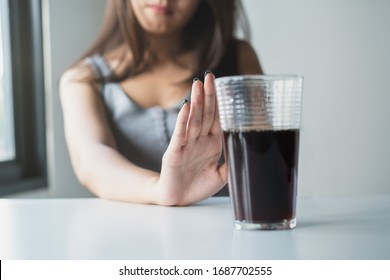 Limits sugar diet in food concepts. Young woman showing bad hand symbol to soft drink soda that have high sugar.