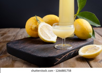 Limoncello in a bottle and a small shot with liquor. The traditional alcoholic beverage of Italy, from citrus. Fresh fruits and drinks. Free space for text.