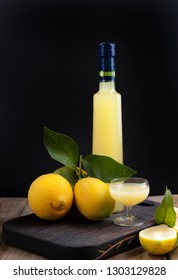 Limoncello in a bottle and a small shot with liquor. The traditional alcoholic beverage of Italy, from citrus. Fresh fruits and drinks. Free space for text