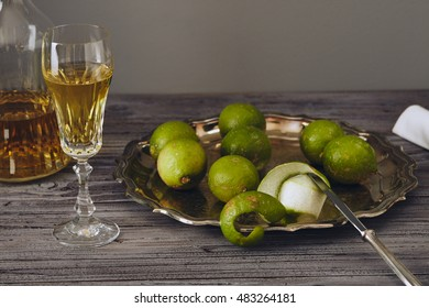 Limoncello in a classic elegant bottle and glass with green lemon on a silver serving plate with a knife
