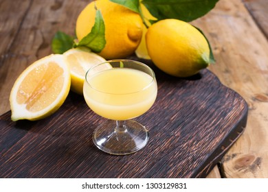 limoncello in a glass and fresh citrus fruits with green leaves. Traditional Italian lemon liqueur. Alcohol on a dark wooden background. Antique drinks from the south