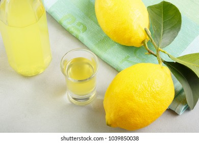 limoncello on a light background. summer traditional Italian drink of home-made liqueur from Sicilian lemons. Alcoholic drink is yellow. articles made of fruits. summer background with fruit