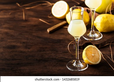 Limoncello, sweet Italian lemon liqueur, traditional strong alcoholic drink. Still life in vintage style, selective focus