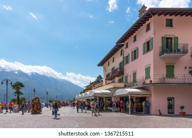Limone sul Garda, Italy - April 30,2018: Picturesque view of Limone sul Garda, Lake Garda, Italy. Beautiful spring day. Embankment with tourists, cafes and shops.