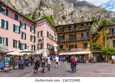 Limone sul Garda, Italy - April 30,2018: Picturesque view of Limone sul Garda, Lake Garda, Italy. Beautiful spring day. Central street with tourists, cafes and shops