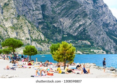 LIMONE SUL GARDA/ ITALY - AUGUST 16, 2015: People at the beach, Limone sul Garda town, Lake Garda (Lago di Garda or Lago Benaco), Brescia province, Lombardy, Italy, Europe