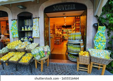 Limone sul Garda, Italy - July 2, 2019: Picturesque view of a common souvenirs shop in Limone sul Garda, Lake Garda, Italy. Central street with tourists, cafes and shops