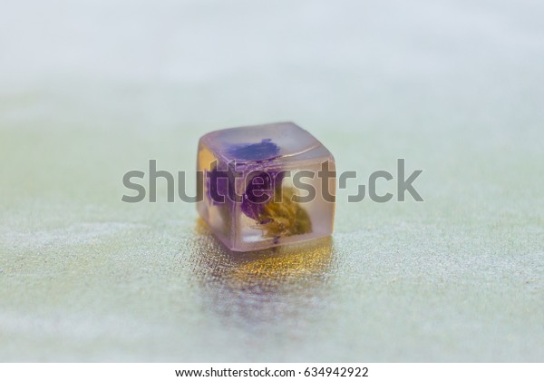 Limonium flowers inside of crystal made of epoxy resin close-up with bokeh on background shallow depth of field