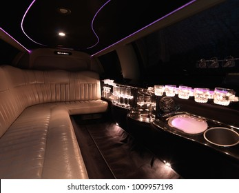 Limousine interior by night with bar, champagne crystal bottles and pink light.