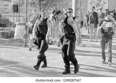 Limoux Aude France. 04/13/19. Three Gerdarmes on patrol at a wine festival. The music was so loud that one young officer had trouble hearing his colleague.