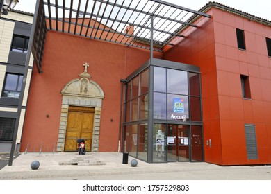 Limoux, Aude, France 06/16/20 Hospital entrance to reception. Original stone arch and wooden doors. Modern glass and steel structure. orange facade, pedestrian walkway, cycle racks