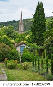 Limoux, Aude, France 06/16/20 Saint Martin church steeple, gardeners shed, trees and shrubs. Distant wooded hillsides and fields.  Vercast sky.