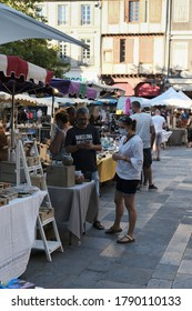 Limoux Aude France 08/04/20 Couple at French market. Man texting. Woman wearing face mask standing by unmasked partner. Souvenir stalls and tables