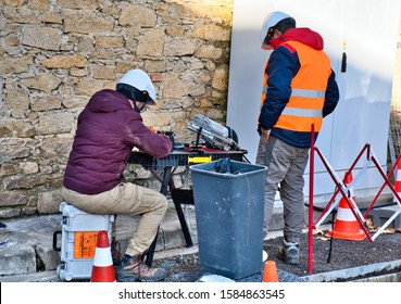 Limoux Aude France 12/10/19 Technicians working in the street installing fibre optic network for high speed internet network. Man operating a fibre connection  machine. Wearing hard hats and Hi Vis
