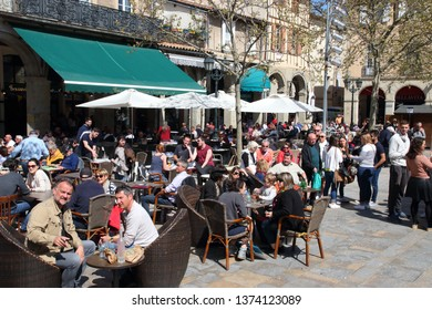 LIMOUX, FRANCE-MARCH 30, 2019: Crowd of people sitting on the terrace of bar at the carnival of Limoux in Aude, Occitanie in the south of France