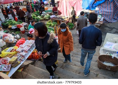 Lincang, Yunnan Province, China- 01.25.2017- People strolling around local street market in countryside town
