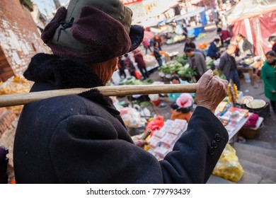 Lincang, Yunnan Province, China- 01.25.2017- Elder man carrying his goods to sell on local market in countryside