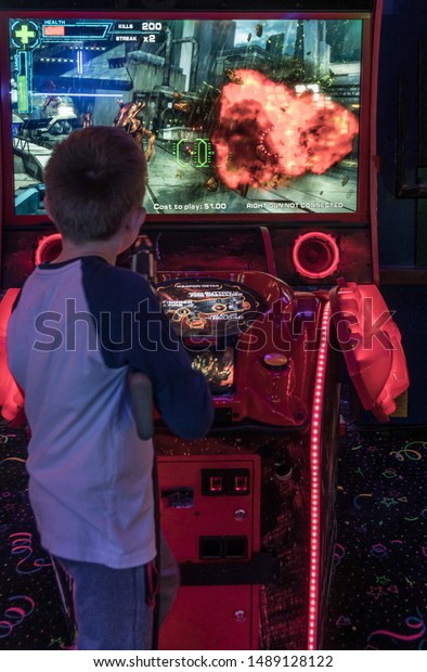 Lincoln City, Oregon - August 24, 2019: Young boy playing colorful violent shooting video arcade game.