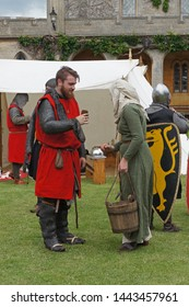 Lincoln, England - June 23, 2019: A lady in medieval costume hands a drink to  a man dressed as a knight during a reenactment at Lincoln Castle, In Lincolnshire.