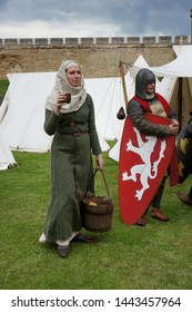 Lincoln, England - June 23, 2019: A lady in medieval costume serves water to knights taking part in a reenactment at Lincoln Castle, In Lincolnshire.