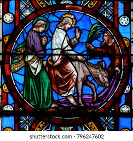 Lincoln, England - Nov 16, 2017: Close up G of Great East Window in Lincoln Cathedral, Stained Glass made by Ward and Hughes (1855); Jesus On A Donkey Riding To Jerusalem