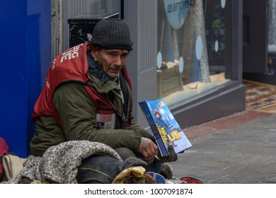 Lincoln, England - Nov 17, 2017: Big Issue Seller Sitting on the Pavement on Lincoln High Street, Shallow Depth of Field