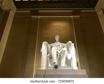 Lincoln Memorial sculpture at night from lower center perspective, wall bathed in golden light. No people. Room for copy in center, left and right of frame.
