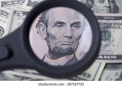 Lincoln on five dollar over heap of dollars United States as a background.