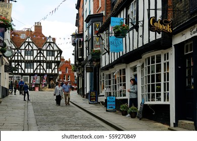 """LINCOLN, UK - JULY 1, 2016: The top of Steep Hill, a popular tourist street in the historic city of Lincoln. In 2011 it was named """"Britain's Best Place"""" by the Academy of Urbanism."""